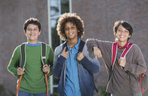 3 boys smiling with backpacks