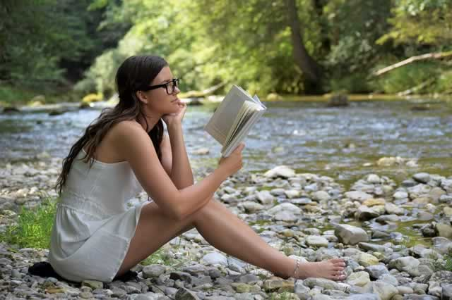 girl reading a book by a creek