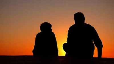 silhouette of father and son talking